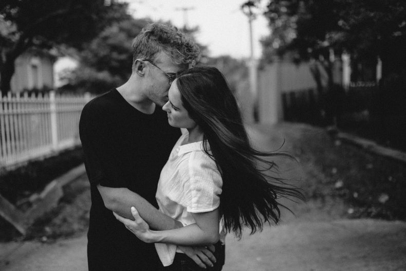 romantic embrace between couple while wind blows her hair