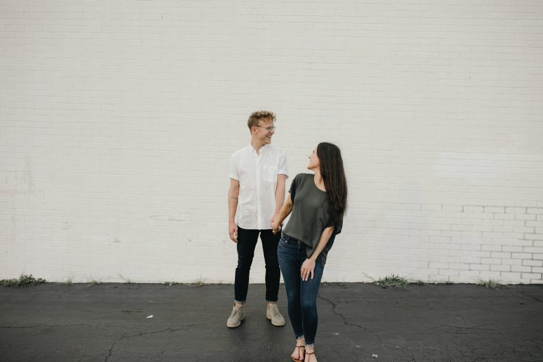 happy couple standing in front of painted white brick wall