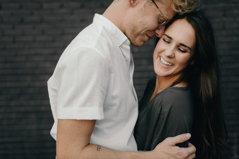 woman smiling while being wrapped up by her fiance in front of black brick wall