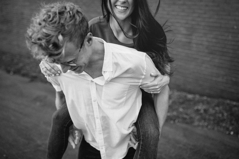 woman riding on man's back outside for engagement photos