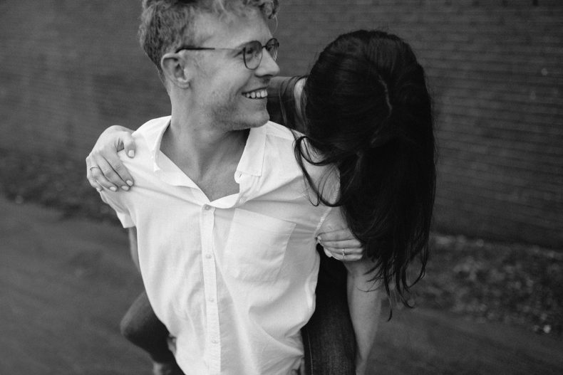 man giving woman a piggy back ride in front of painted brick wall