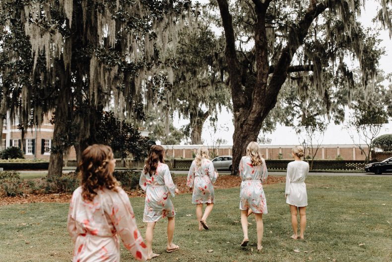 four bridesmaids in floral robes walking with bride in solid white robe on ford plantation property